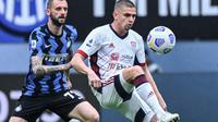 Gelandang Inter Milan, Marcelo Brozovic berduel dengan pemain Cagliari saat kedua tim bertemu di ajang Liga Italia 2020/2021, Minggu (11/04/2021). (Alberto PIZZOLI / AFP)