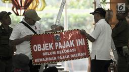 Tim gabungan dari Badan Pelayanan Pajak, Kecamatan Cempaka Putih, dan Satpol PP menyiapkan stiker tunggak pajak di salah satu kios Green Pramuka Square Mall, Jakarta, Rabu (7/11). (Merdeka.com/Iqbal S. Nugroho)