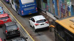 Kendaraan menerobos jalur transjakarta menghindari macet di Jalan MH Thamrin, Jakarta, Kamis (31/5). Tingginya antusiasme warga untuk berbuka puasa di rumah menyebabkan jalan-jalan protokol di Ibukota dipadati kendaraan. (Liputan6.com/Immanuel Antonius)