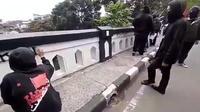 Kelompok berbaju hitam mencoretkan tulisan protes di Jembatan Kahuripan yang berstatus cagar budaya di Kota Malang (capture)