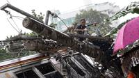Petugas mengevakuasi gerbong KRL yang anjlok di Kebon Pedes, Bogor, Jawa Barat, Minggu (10/3). Kecelakaan KRL jurusan Jatinegara-Bogor tersebut menyebabkan enam orang luka-luka, termasuk masinis kereta. (Liputan6.com/Immanuel Antonius)