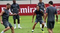 Pemain Arsenal, Mesut Ozil dan rekan setimnya menjalani latihan untuk kompetisi pramusim International Champions Cup (ICC) 2018 di Singapura, Rabu (27/5). Menjelang duel kontra Atletico Madrid, Ozil dkk menikmati sesi latihan ringan. (AFP/Roslan RAHMAN)