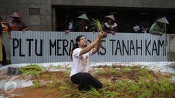 Seorang petani saat menggelar aksi menanam padi di depan Kedubes Jepang, Jakarta, Senin (5/12). Dalam aksinya, mereka menuntut ganti rugi paska penutupan akses lahan pertanian mereka karena pembangunan PLTU batu bara Batang. (Liputan6.com/Faizal Fanani)