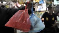 Warga menunjukkan barang belanjaan yang dibawa menggunakan kantong plastik sekali pakai di Pasar Tebet Barat, Jakarta, Kamis (6/2/2020). Masih banyak pedagang maupun pembeli yang menggunakan kantung plastik sebagai tempat bawaan membawa belanjaan. (merdeka.com/Iqbal S Nugroho)
