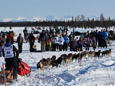 Penonton menyaksikan musher Jessie Holmes meninggalkan garis start Iditarod Sled Dog Race di Deshka Landing di Willow, Alaska, Minggu (7/3/2021). Sled Dog Trail merupakan lomba balap kereta luncur yang ditarik oleh anjing yang digelar tiap tahun. (Marc Lester/Anchorage Daily News via AP)