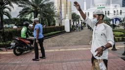 Petugas mengajak pengendara yang melintas mengambil takjil secara drive thru di Kompleks Masjid Al-Azhar, Jakarta, Selasa (13/4/2021). Pengelola Masjid Al-Azhar menyiapkan 500 bungkus takjil per hari yang dibagikan secara drive thru guna mencegah penyebaran COVID-19. (merdeka.com/Iqbal S. Nugroho)