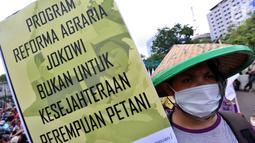 Massa tani memapangkan spanduk tuntutan dalam unjuk rasa di depan Istana Negara, Jakarta, Rabu (27/9). Dalam aksinya yang memperingati Hari Tani Nasional, mereka meminta Presiden segera memperbaiki ketimpangan struktur agraria. (Liputan6.com/Johan Tallo)
