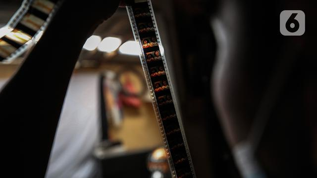 Adul (29) mengecek film seluloid 35mm untuk pertunjukan layar tancap di gudang rumahnya di Jakarta, Rabu (28/4/2021). Saat ini Adul dan ayahnya hanya bisa merawat peralatan dan film seluloid 35mm di gudang rumah mereka. (Liputan6.com/Johan Tallo)