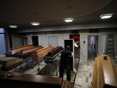 Seorang pekerja memindahkan peti jenazah untuk dibakar di sebuah krematorium di Ostrava, Republik Ceko pada 7 Januari 2021. Krematorium terbesar di Ceko dan satu-satunya di wilayah itu telah kewalahan dalam mengkremasi jasad-jasad korban COVID-19 yang terus bertambah. (AP Photo/Petr David Josek)