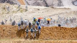 Aktivis iklim mamasuki tambang batu bara lignit Garzweiler di Garzweiler, Jerman barat, Sabtu (22/6/2019). Para aktivis mengenakan pakaian putih dan membawa kantong tidur. (Marcel Kusch/DPA/AFP)
