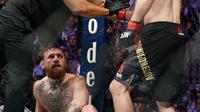 Khabib Nurmagomedov (kanan) ditahan oleh wasit Herb Dean setelah bertarung melawan Conor McGregor selama pertarungan UFC 229 di Las Vegas, AS (6/10). Nurmagomedov menang atas McGregor di ronde keempat. (AP Photo/John Locher)