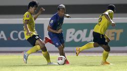 Striker Arema FC, Dendi Santoso (tengah) berusaha melewati dua pemain Barito Putera dalam laga matchday ke-2 Grup A Piala Menpora 2021 di Stadion Manahan, Solo, Kamis (25/3/2021). Arema FC sementara tertinggal 0-2 dari Barito Putera di babak pertama. (Bola.com/Arief Bagus)