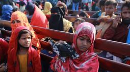 Pengungsi Rohingya duduk di kapal Angkatan Laut Bangladesh saat mereka dipindahkan ke pulau rawan banjir yang kontroversial, Bhashan Char di Teluk Benggala, di Chittagong (29/12/2020). Pada gelombang pertama lebih dari 1.600 pengungsi direlokasi. (AFP/Rehman Asad)