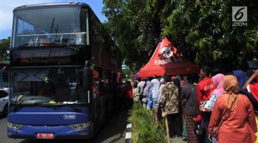 Antrean warga menaiki bus tingkat untuk wisata keliling Ibu Kota di depan Masjid Istiqlal, Jakarta, Sabtu (31/3). Libur tiga hari di penghujung Maret 2018 dimanfaatkan untuk berkeliling Jakarta menggunakan bus tingkat City Tour. (Merdeka.com/Imam Buhori)