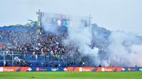 Suporter menyalakan flare pada laga Arema FC Vs Bali United di Stadion Kanjuruhan, Kab. Malang, Senin (16/12/2019). (Bola.com/Iwan Setiawan)