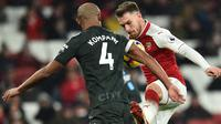 Bek Manchester City, Vincent Kompany berebut bola dengan gelandang Arsenal, Aaron Ramsey pada laga pekan ke-28 Premier League di Emirates Stadium,  Jumat (2/3). Manchester City mempermalukan Arsenal dengan skor telak 3-0. (Glyn KIRK/AFP)