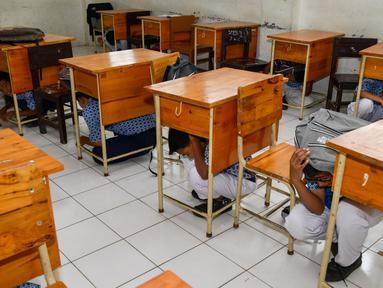 Sejumlah siswa berlindung di bawah meja saat simulasi bencana gempa dan tsunami di sebuah sekolah di Banda Aceh, Aceh, Rabu (9/10/2019). Para siswa dibekali wawasan tanggap darurat bencana dan pemberian pertolongan pertama pada korban gempa. (Photo by CHAIDEER MAHYUDDIN / AFP)