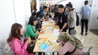 Sejumlah pelamar mengisi berkas lamaran saat menghadiri Job for Career di Stadion Gelora Bung Karno Jakarta, Rabu (30/9/2015). Tingginya angka pencari kerja menjadikan bursa kerja ramai peminat. (Liputan6.com/Helmi Fithriansyah)