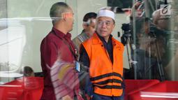 Tersangka Gubernur Aceh Irwandi Yusuf (kanan) usai menjalani pemeriksaan di Gedung KPK, Jakarta, Kamis (26/7). Irwandi Yusuf memakai rompi tahanan dan kopiah merah putih. (Merdeka.com/Dwi Narwoko)