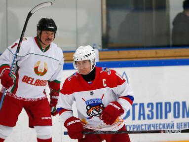 Presiden Rusia Vladimir Putin (kanan) dan Presiden Belarusia Alexander Lukashenko mengikuti Night Hockey League di Sochi, Rusia, Jumat (7/2/2020). Putin dan Lukashenko bermain hoki bersama saat jeda pembicaraan ekonomi antara kedua negara. (AP Photo/Alexander Zemlianichenko, Pool)