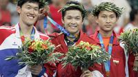 Pebulutangkis tunggal putra, Taufik Hidayat (tengah) berhasil kalahkan Shon Seung-mo dari Korea Selatan di babak final Olimpiade Athena 2004. Dirinya menjadi satu-satunya kontingen yang mampu bawa medali emas untuk Indonesia di ajang Olimpiade itu. (Foto: AFP)
