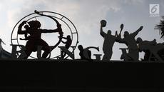 Pekerja membersihkan ornamen orang memanah di gerbang masuk jalan Pintu Satu Senayan, Jakarta, Jumat (20/7). Jelang perhelatan Asian Games 2018, sejumlah fasilitas penunjang di kawasan Gelora Bung Karno terus dipercantik. (Liputan6.com/Helmi Fithriansyah)