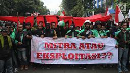Sejumlah pengemudi ojek online membentangkan spanduk saat menggelar aksi di seberang Istana Merdeka, Jakarta, Selasa (27/3). Dalam aksinya mereka menuntut pemerintah melakukan penetapan tarif standar dengan nilai yang wajar. (Liputan6.com/Arya Manggala)