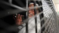 Terpidana kasus terorisme Abu Bakar Baasyir melambaikan tangan kepada media ketika di mobil tahanan usai menjalani persidangan di Jakarta, (16/06/2011). (AFP Photo/Romeo Gacad)