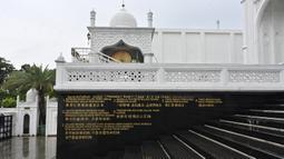 Terjemahan Surat Al-Fatihah terlihat dalam bahasa Inggris, Bahasa Indonesia dan aksara China di dinding menuju masjid Ramlie Musofa yang kosong selama bulan suci Ramadan karena pandemi virus coronavirus COVID-19 di Jakarta (4/5/2020). (AFP/Adek Berry)