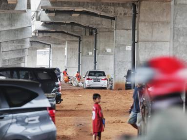 Petugas kebersihan beraktivas dekat sejumlah mobil yang terparkir di bawah kolong tol Becakayu Kalimalang, Jakarta Timur, Selasa (12/2). Lahan kosong di bawah kolong tol Becakayu disalahgunakan menjadi parkir liar. (Liputan6.com/Faizal Fanani)