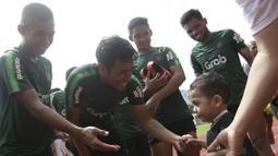 Pemain Timnas Indonesia U-23, Hanif Sjahbandi, menyapa seorang anak yang datang ke Stadion Madya, Jakarta, Rabu (13/3). Sejumlah anak dari Yayasan Rumah Harapan Indonesia datang menemui Timnas U-23 (Bola.com/Vitalis Yogi Trisna)