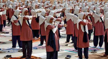 Siswa mengikuti gerakan Yoga jelang Hari Yoga Dunia di Ahmedabad , India , (16/6). Setiap tanggal 21 Juni, seluruh dunia memperingati Hari Yoga Sedunia. (REUTERS / Amit Dave)