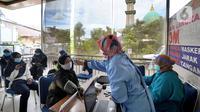 Petugas mengecek suhu tubuh tenaga kesehatan berusia lanjut sebelum menerima suntikan vaksin COVID-19 Sinovac di Puskesmas Kecamatan Jagakarsa, Jakarta, Kamis (11/2/2021). Sekitar 11 ribu nakes lansia berusia di atas 60 tahun menjadi prioritas penerima vaksin covid-19. (merdeka.com/Arie Basuki)