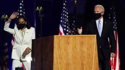 Presiden terpilih Joe Biden dan Wakil Presiden terpilih Kamala Harris melambaikan tangan ke kerumunan saat menyampaikan pidato kemenangan Pilpres AS 2020 di Wilmington, Delaware, Amerika Serikat, Sabtu (7/11/2020). Joe Biden dan Kamala Harris memenangkan Pilpres AS 2020. (AP Photo/Andrew Harnik)