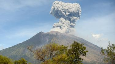 Asap bercampur abu vulkanis keluar dari kawah Gunung Agung terlihat dari desa Tulamben, Karangasem, Bali, Selasa (3/7). Pagi ini, Gunung Agung kembali meletus disertai abu vulkanik setinggi 2.000 meter di atas puncak. (AFP/SONNY TUMBELAKA)