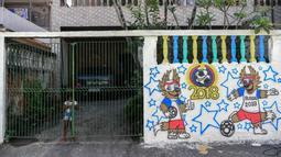 Seorang gadis berdiri di belakang gerbang pada sebuah mural Piala Dunia 2018 di dinding jalanan Camboata, Rio de Janeiro, Brasil, Kamis (31/6). (Fabio TEIXEIRA/AFP)