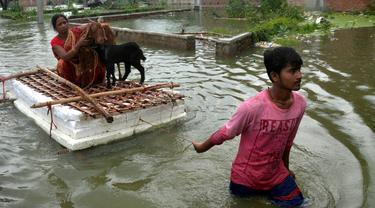 Seorang anak mengangkut ibu beserta hewan-hewan ternaknya menggunakan perahu darurat di sebuah desa di Distrik Muzaffarpur, Negara Bagian Bihar, India timur, 26 Juli 2020. Sedikitnya 10 orang tewas dan hampir 1,5 juta orang terkena dampak akibat banjir di 11 distrik di Bihar. (Xinhua/Partha Sarkar)