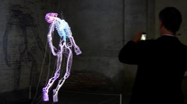 Pengunjung mengambil gambar karya seni buatan seniman Bahamian Tavares Strachan saat pratinjau pers menjelang pembukaan pameran International Venice Biennale di Venesia, Italia, Rabu (8/5/2019). International Venice Biennale ke-58 ini bertema 'May You Live In Interesting Times'. (TIZIANA FABI/AFP)