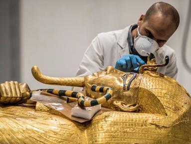 Arkeolog merestorasi sarkofagus atau peti mati emas Firaun Tutankhamun di laboratorium restorasi Grand Egyptian Museum (GEM), Giza, Mesir, Senin (13/4/2020). Firaun Tutankhamun merupakan Raja Mesir Kuno yang memerintah antara tahun 1342-1325 SM. (Khaled DESOUKI AFP)