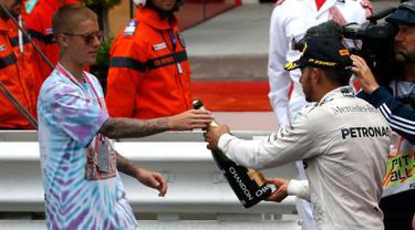 Pembalap Mercedes F1 Lewis Hamilton memberikan sampanye kepada penyanyi Justin Bieber usai berhasil menjuarai Grand Prix di Monaco, (29/5). Hamilton menjadi yang tercepat dengan mencatatkan waktu satu jam 59 menit 29,133 detik. (REUTERS/Eric Gaillard)