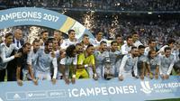 Cristiano Ronaldo (kiri) berfoto bersama timnya saat meraih trofi Piala Super Spanyol 2017 bersama rekannya di Santiago Bernabeu stadium, Madrid, (16/8/2017). Real menang agregat 5-1. (AP/Francisco Seco)