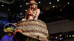 Seorang model memperagakan busana rancangan desainer Kolombia, Laura Campo selama BioFashion Show di Cali  pada 17 November 2018. Ajang ini menampilkan gaun-gaun unik yang terbuat dari tanaman hidup, bunga dan unsur organik lain. (Luis ROBAYO/AFP)