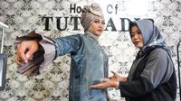 Perancang busana muslim asal Solo, Tuty Adib menunjukkan salah satu karya yang akan dipamerkan saat fashion show di London, Jumat (16/2).(Liputan6.com/Fajar Abrori)