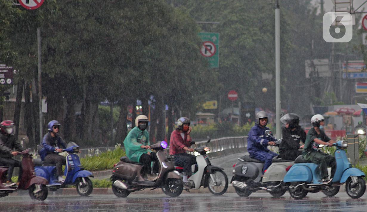 Pengendara sepeda motor menggunakan jas hujan saat berkendara di kawasan Bundaran HI, Jakarta, Minggu (24/1/2021). Badan Meteorologi Klimatologi dan Geofisika (BMKG) mencatat sebagian besar wilayah Indonesia telah memasuki masa puncak musim hujan. (Liputan6.com/Herman Zakharia)