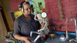 Ahmed Hussein memamerkan sebuah patung di bengkelnya di Giza, Mesir, pada 5 September 2020. Dua pemuda Mesir berhasil mengubah hobi mereka mendaur ulang barang bekas seperti besi tua menjadi berbagai dekorasi dan furnitur rumah sebagai sumber penghasilan yang stabil. (Xinhua/Ahmed Gomaa)