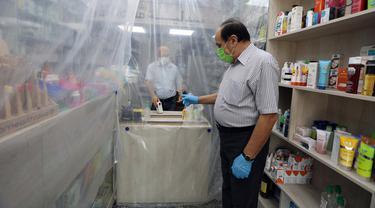 Lapisan plastik digunakan untuk mengurangi kontak fisik antara pegawai dengan pembeli di sebuah apotek di Baghdad, Irak, Selasa (14/4/2020). Menjaga jarak fisik atau physical distancing dinilai langkah paling tepat untuk mengurangi penyebaran virus corona COVID-19. (Xinhua)