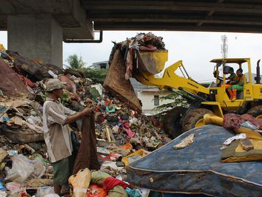 Petugas PPSU DKI Jakarta menggunakan alat berat mengangkut sampah di bawah Tol Becakayu, Cipinang Melayu, Jakarta Timur, Rabu (8/1/2020). Sampah sisa banjir tersebut selanjutnya diangkut ke TPA Bantar Gebang. (merdeka.com/Magang/Muhammad Fayyadh)