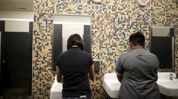Dua siswa mencuci tangan mereka di toilet netral gender pertama di Santee High School, Los Angeles, California, AS, Senin (18/4). Toilet disediakan sebagai langkah mendukung dan menampung siswa transgender. (REUTERS/Lucy Nicholson)