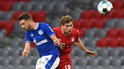 Gelandang Bayern Munchen, Leon Goretzka, berebut bola dengan penyerang Schalke, Mark Uth, pada laga Liga Jerman di Allianz Arena, Sabtu (19/9/2020) dini hari WIB. Bayern Munchen menang 8-0 atas Schalke. (AFP/Christof Stache)