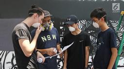 Siswa Menengah dan Menengah Atas Jakarta Intercultural School (JIS) dan Darbotz, seniman Mural Art kenamaan Indonesia (kedua kiri), tengah berdiskusi di workshop melukis mural di dinding sekolah, Jakarta, Sabtu (7/4). (Liputan6.com/Herman Zakharia)